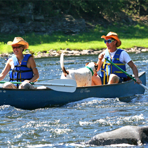 couple and their dog in a canoe on the river Indian Head Canoeing Rafting Kayaking Tubing Delaware River