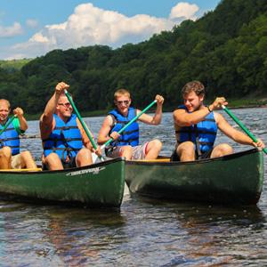 two groups of canoers in friendly race Indian Head Canoeing Rafting Kayaking Tubing Delaware River