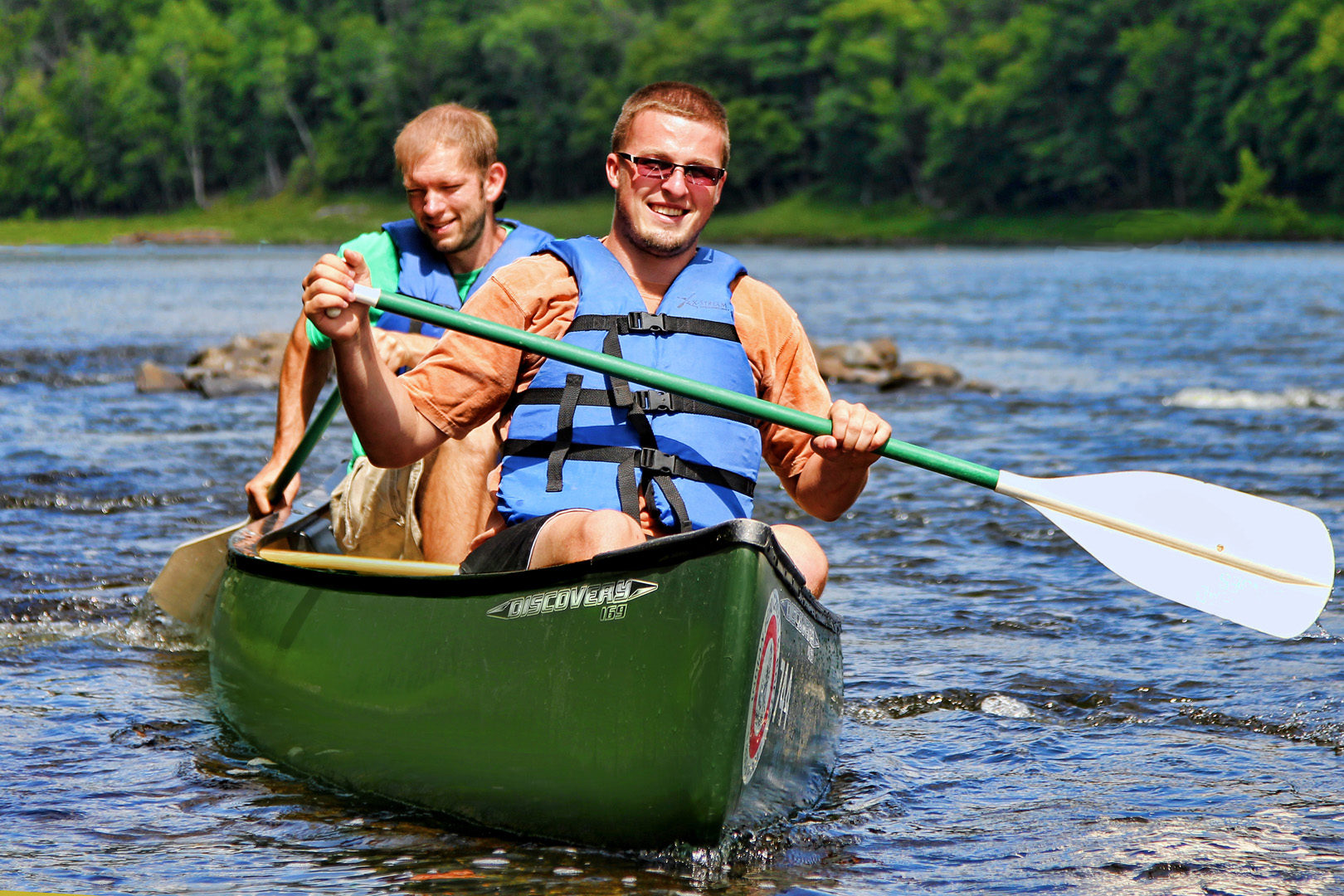 two guys enjoying their canoe ride on the river Indian Head Canoeing Rafting Kayaking Tubing Delaware River