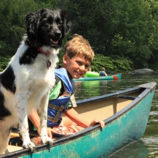 young boy and dog enjoying their canoe ride Indian Head Canoeing Rafting Kayaking Tubing Delaware River