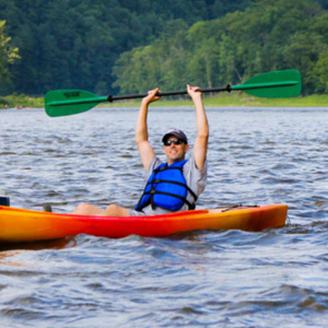 man holding paddle over his head while sitting in kayak Indian Head Canoeing Rafting Kayaking Tubing Delaware River