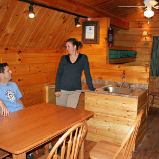 couple in kitchen in log cabin Indian Head Canoeing Rafting Kayaking Tubing Delaware River