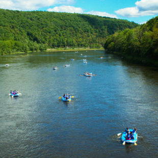 several groups on rafts on Delaware River with green tree views Indian Head Canoeing Rafting Kayaking Tubing Delaware River