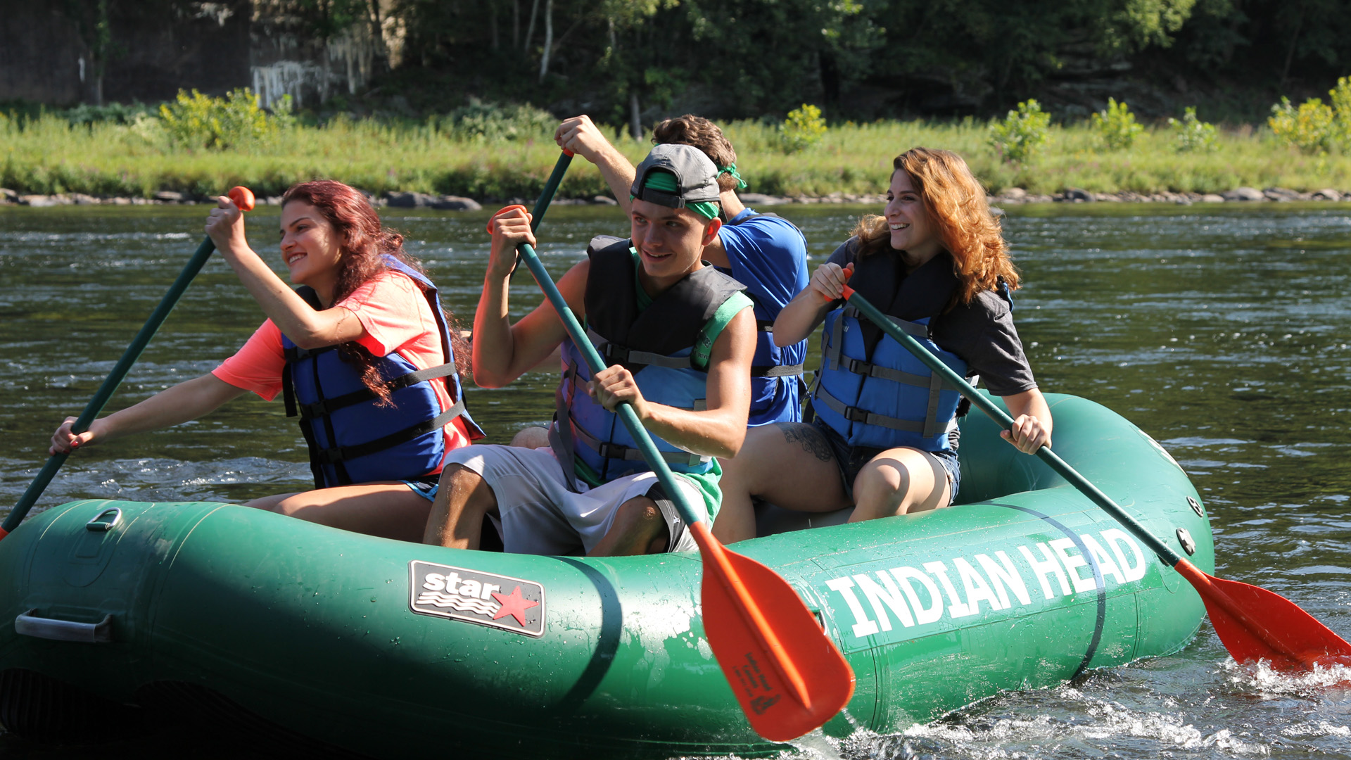 group of teens navigating calm waters in raft Indian Head Canoeing Rafting Kayaking Tubing Delaware River