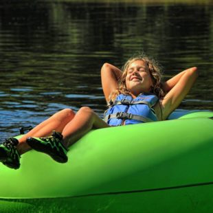 young girl soaking up sun in tube Indian Head Canoeing Rafting Kayaking Tubing Delaware River